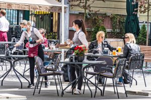 Vilnius, Lithuania - May 3 2020: Waitresses with a mask and gloves disinfecting the table of an outdoor bar, café or restaurant with blonde girls at the table, reopening after quarantine restrictions