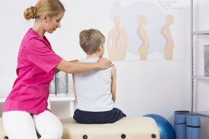 Physiotherapist correcting body posture of a small boy