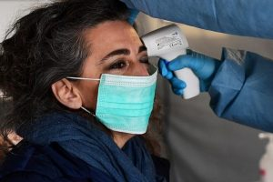 A nurse controls the temperature of a woman in the a pre-triage medical tent in front of the Cremona hospital, in Cremona, northern Italy, on March 4, 2020. - Italy will recommend people stop kissing in public, avoid shaking hands and keep a safe distance from each other to limit the spread of the novel coronavirus. Other measures to be approved by the government, which has borne the brunt of the COVID-19 disease, includes a plan to play all football matches behind closed doors. (Photo by Miguel MEDINA / AFP)